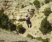 A person going down on Caption Zipline's zipline above the canyon.